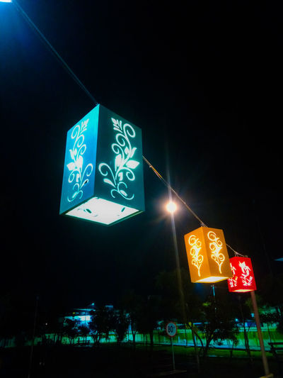 Low angle view of illuminated sign on street at night