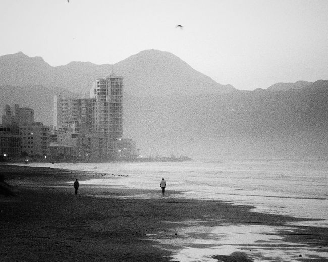 Wandering the beach at sunrise Beach Outdoors City Moody Grainy Black And White People Architecture Nature Sky Water Alone