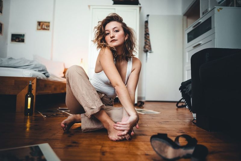 Indoors  Sitting One Person Full Length Flooring Young Adult Hardwood Floor Wood Home Interior Young Women Domestic Room Adult Women Lifestyles Real People Hairstyle Long Hair Casual Clothing Hair Beautiful Woman