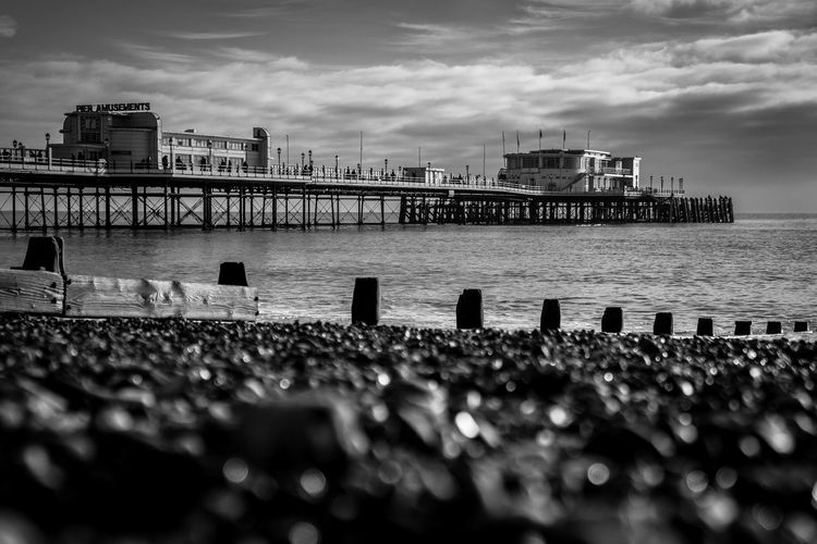 Surface level of worthing pier over river against cloudy sky