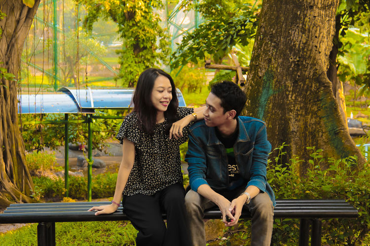 Portrait of couple face to face sitting on bench at park