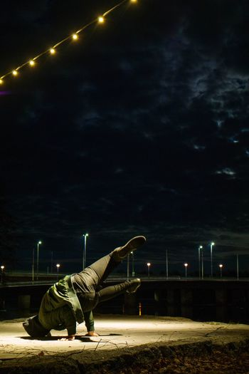 Side view of woman lying down on street against sky at night