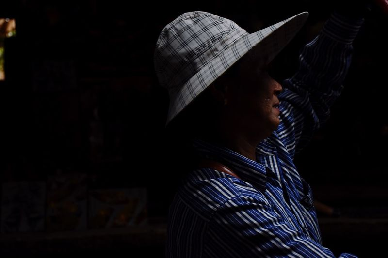 Hard work, dark days, a lifetime adventure. Man Working Working Hard Thailand Thai Boat Boating Hat Asian  Asian Culture Dark Low Light Portrait Shadow Darkness And Light Blue Shirt Countryside