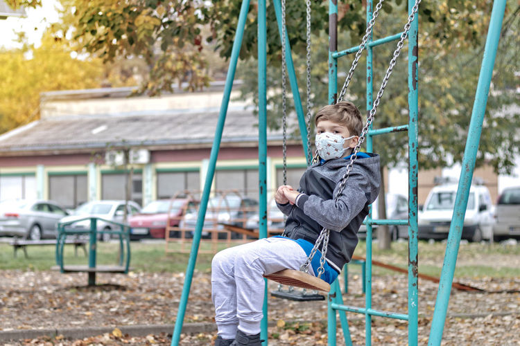 Boy playing on swing at playground