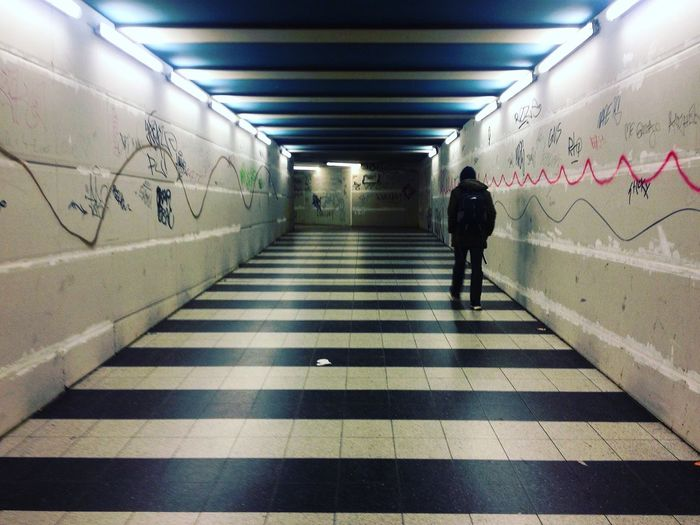Rear view of woman walking in subway tunnel