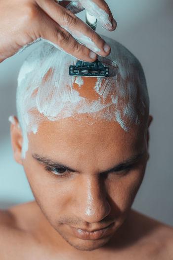 Close-up of man shaving head