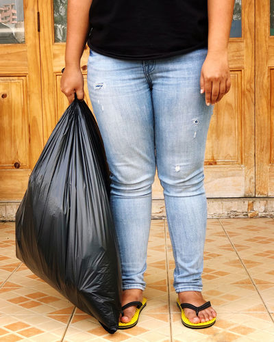 A asian woman carrying a black trash bags to leave the house Low Section Jeans Casual Clothing Human Leg Indoors  Flooring Standing Human Body Part Real People Lifestyles Body Part Adult Hardwood Floor Wood Front View Women Leisure Activity Human Foot Tiled Floor
