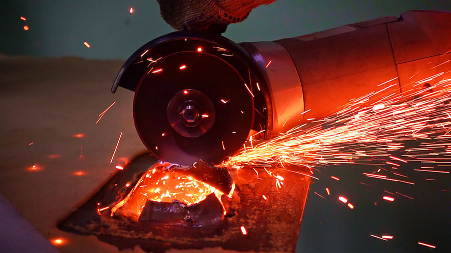 Close-up of sparks emitting from electric saw in factory
