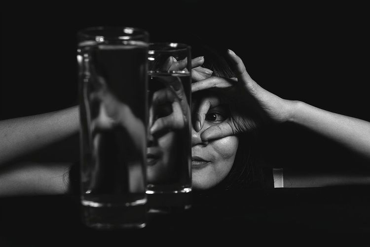 Close-up of woman gesturing over eyes seen through glasses of water