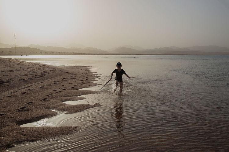 Boy walking on beach against sky