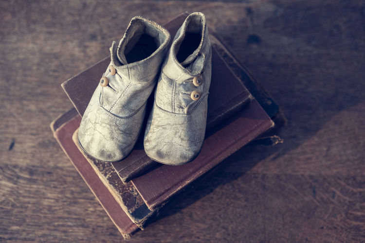 Vintage baby booties on a stack of vintage books Antique Baby Books Boots Old Fashioned Retro Accessories Booties Brown Childhood Clothing Dress Shoe Education High Angle View Leather No People Old Personal Accessory Shoes Still Life Table Vintage Wood Wood - Material Worn