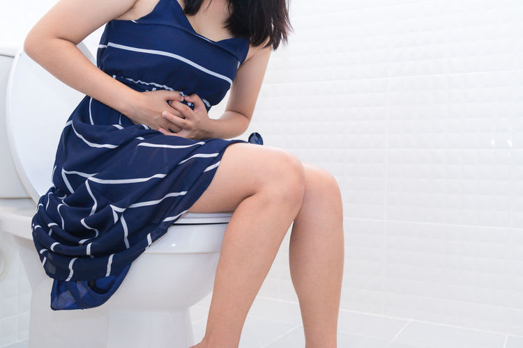 Midsection of woman with hands on stomach sitting in toilet at home