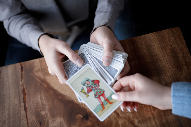 Midsection of woman holding paper at table