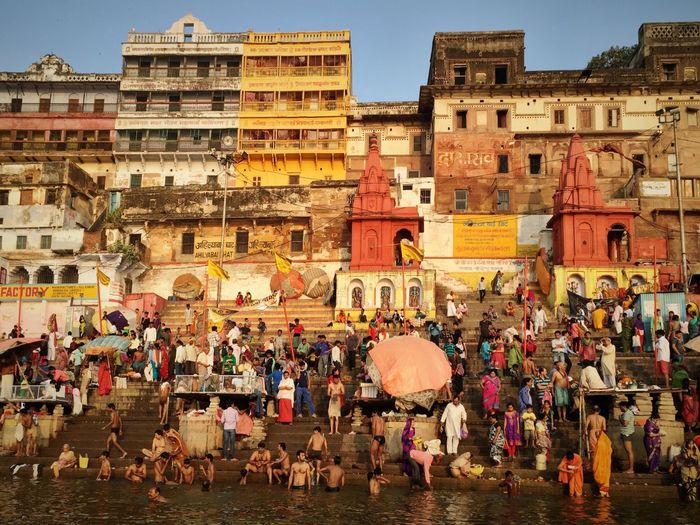 People By Ganges River Against Building