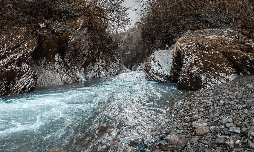 Stream flowing through rocks during winter