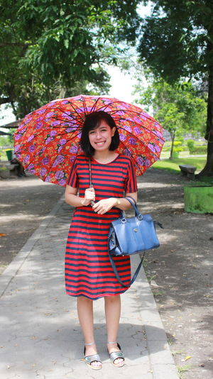 Full length of smiling woman standing in rain