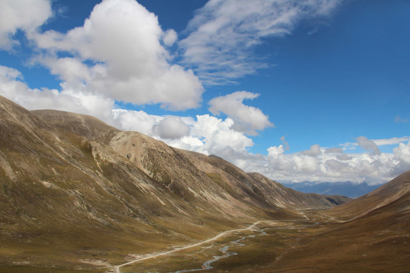 View of mountains, dirt road and stream with the dramatic sky in Tibet, China Beauty In Nature Cloud - Sky Day Grass Landscape Mountain Mountain Peak Mountain Ridge Nature No People Outdoors Rocks Scenics Sky Stones Sunlight Sunny Tibet