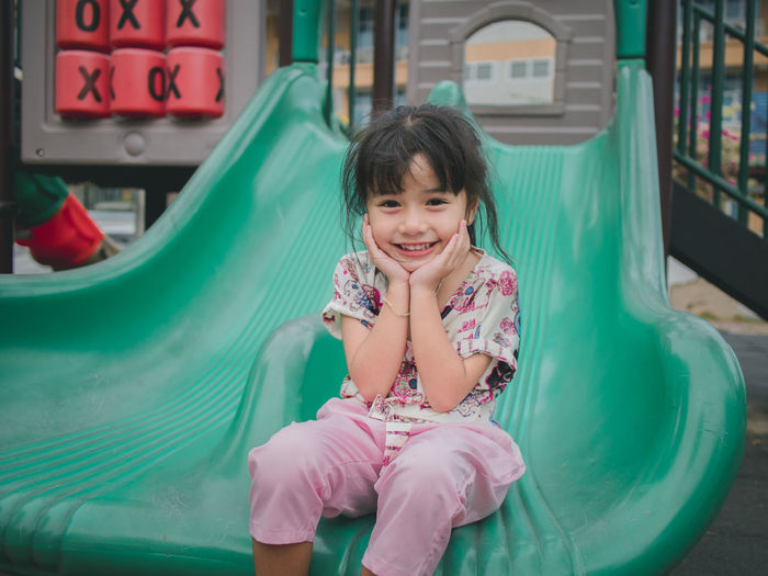 cute asian girl happy play on slide Childhood Child One Person Girls Front View Real People Happiness Smiling Innocence Sitting Portrait Looking At Camera Cute Leisure Activity Lifestyles Women Enjoyment Females Bangs Outdoors Hairstyle Outdoor Play Equipment