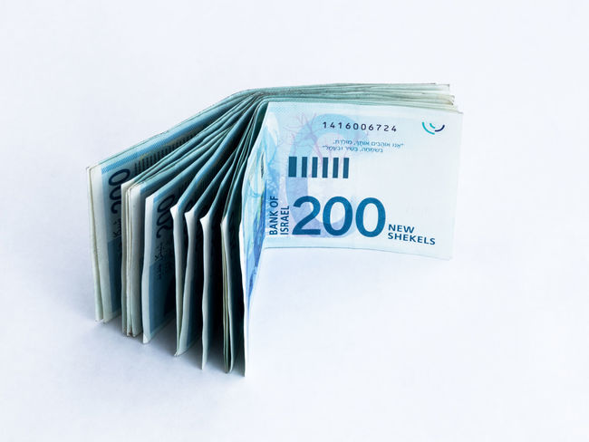 Several new banknotes worth 200 Israeli new shekels on a white background Wealth Banknotes Business Currency Economy Foreign Rich Bank Banknote Cash Close-up Commerce Credit Debt Economic Finance Investment Israel Money Paper Pay Profit Saving Shekel White Background