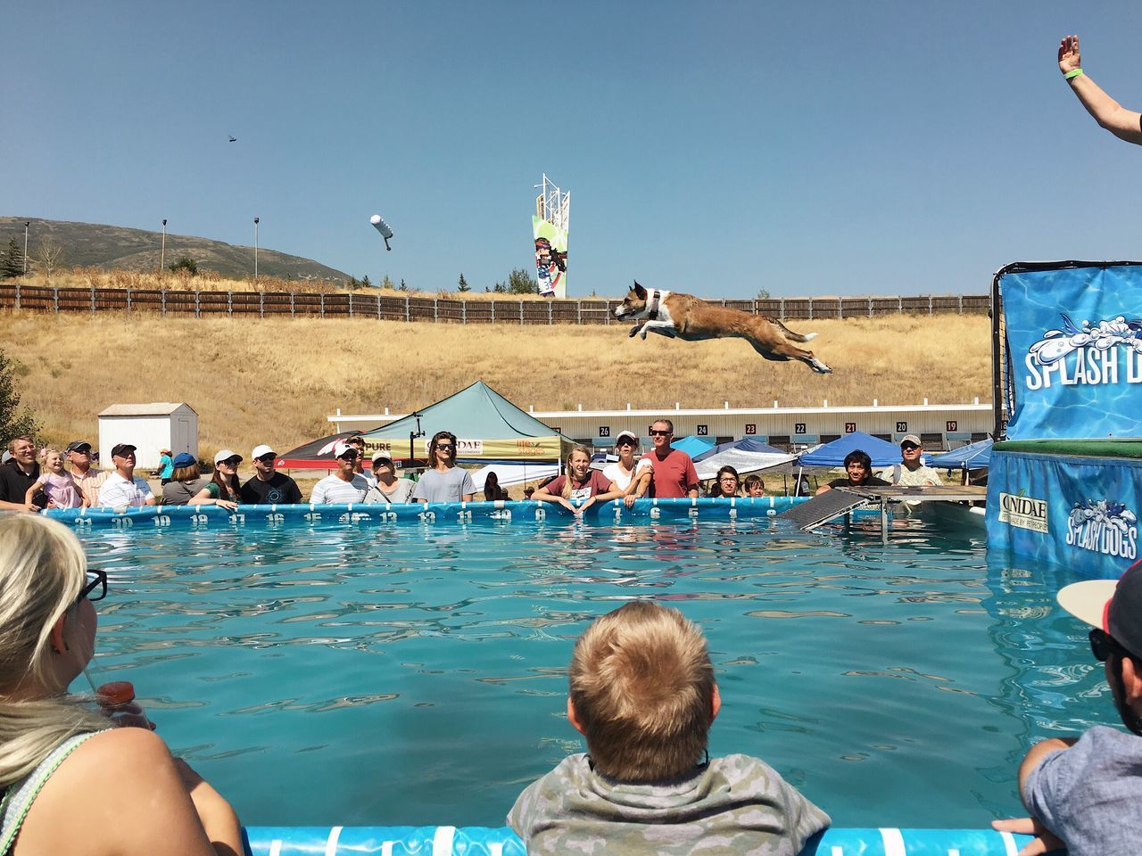 water, group of people, real people, nature, sky, lifestyles, day, architecture, men, built structure, large group of people, clear sky, building exterior, leisure activity, adult, crowd, women, mid-air, outdoors, swimming pool