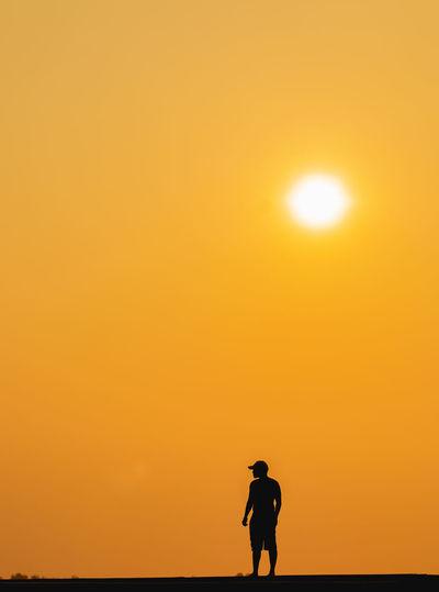 Silhouette man standing on land against orange sky