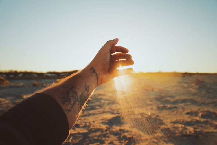 Midsection of person holding sun shining on land
