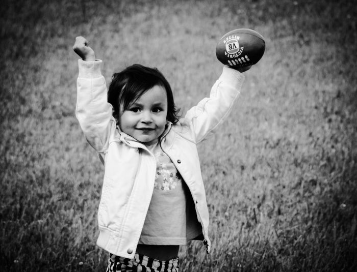 Portrait Of Happy Girl Holding Rugby Ball With Arms Raised Standing On Field