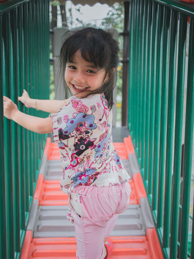 Smiling little girl on the playground Childhood Child Real People Portrait Girls Females Women Looking At Camera One Person Casual Clothing Smiling Happiness Staircase Railing Lifestyles Leisure Activity Full Length Innocence Outdoors Hairstyle Human Arm