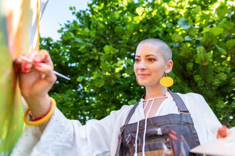Beautiful young woman relaxing while painting an art canvas outdoors in her garden.