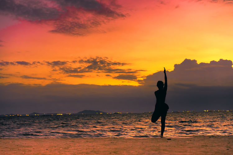 Full Length Of Silhouette Young Woman Practicing Yoga On Shore At Beach During Sunset
