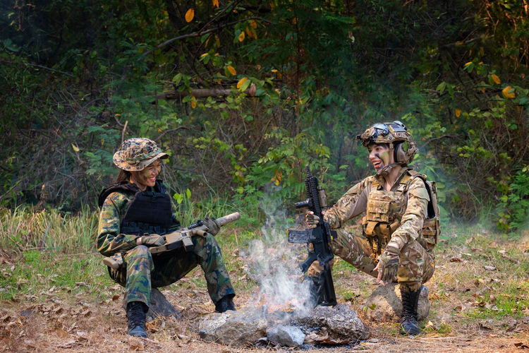Smiling female soldiers sitting at campfire
