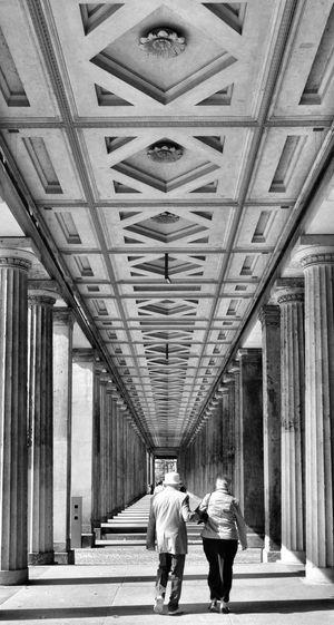 Full Length Men Women Walking Rear View City Architectural Column Illuminated Ceiling Corridor
