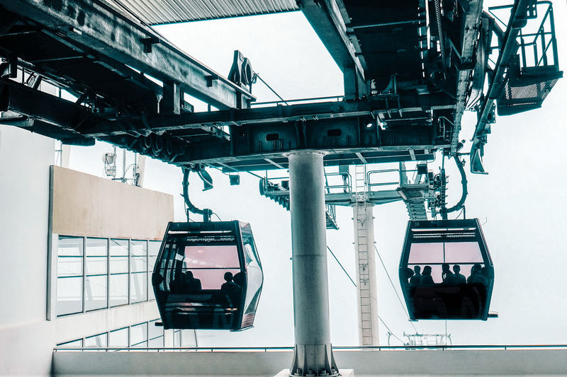 Silhouette people sitting in overhead cable car seen from glass window
