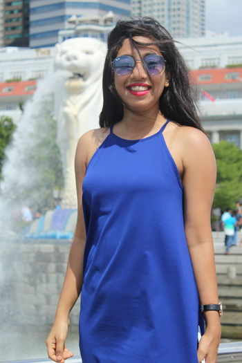 Portrait of young woman wearing sunglasses standing in city