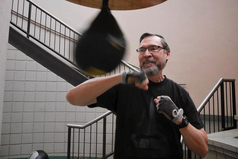 Smiling senior man practicing boxing at gym