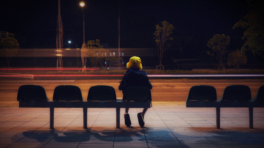 Rear view of boy sitting on chair at night