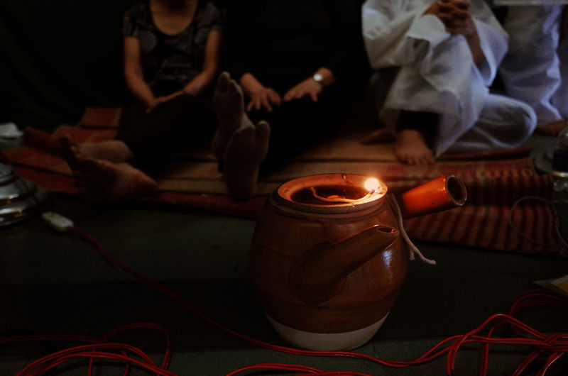 Adult Burning Celebration Close-up Diwali Diya - Oil Lamp Flame Focus On Foreground Heat - Temperature Human Body Part Human Hand Human Leg Indoors  Low Section Men Night Oil Lamp One Person People Real People Vietnamese's Funeral Women