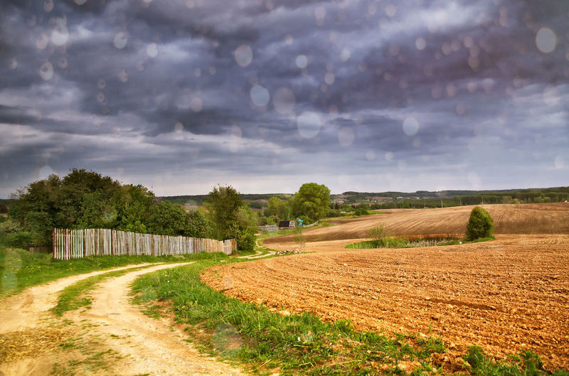 View of farm against cloudy sky