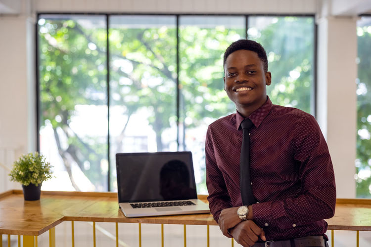 Portrait of a smiling young man standing on table
