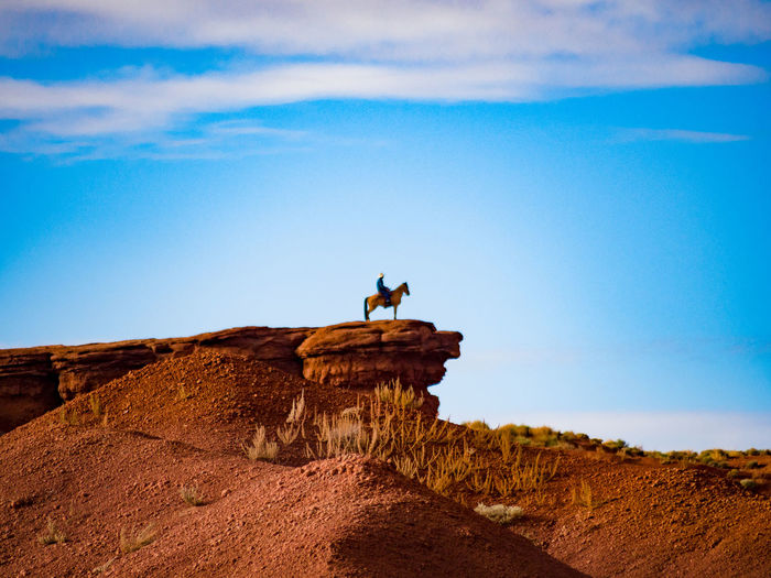 Low Angle View Of Man With Horse On Rock Against Sky