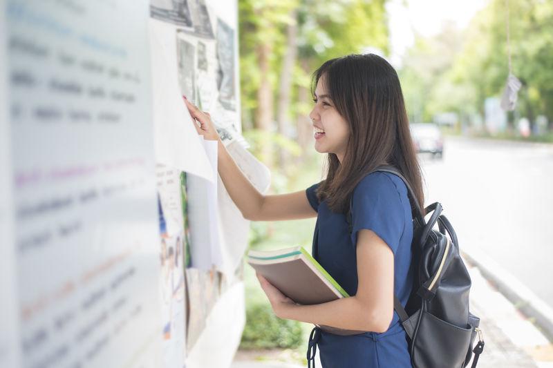Portrait of smiling university student checking test result on bulletin board
