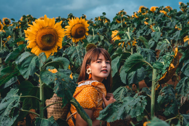 Portrait of girl with sunflowers in background