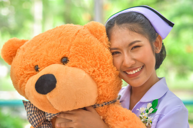 Smiling Young Nurse With Teddy Bear Against Window