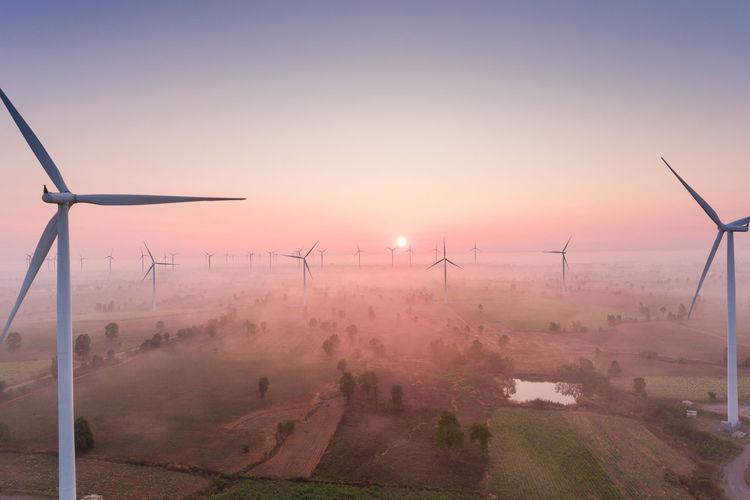 Windmills on landscape against sky during sunset
