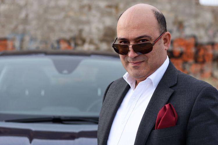 Portrait of man wearing sunglasses and suit against car