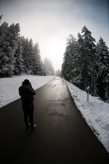 Rear view of man standing on road amidst snow covered pine trees during winter
