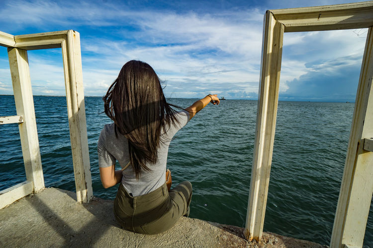 Rear view of woman sitting by sea against sky