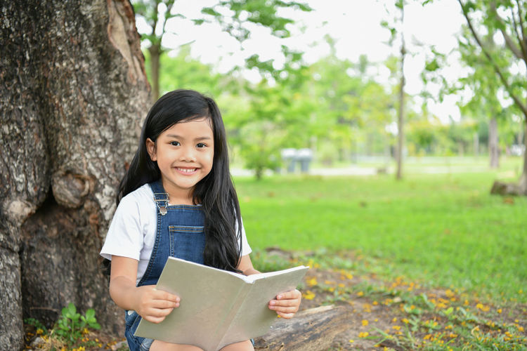 Portrait Of Smiling Girl Holding Book While Sitting Against Tree At Park