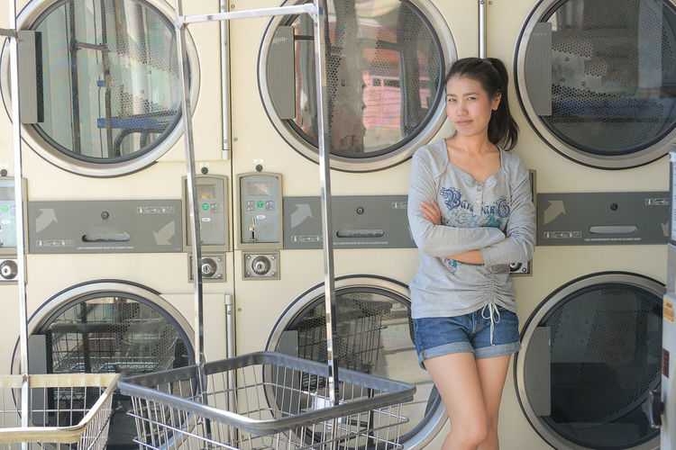 Portrait of woman standing against washing machines in laundromat
