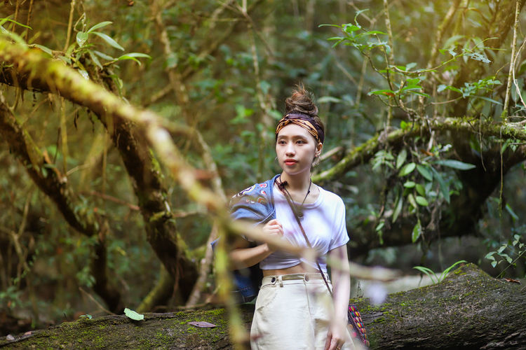 Thoughtful young woman standing by log against trees in forest
